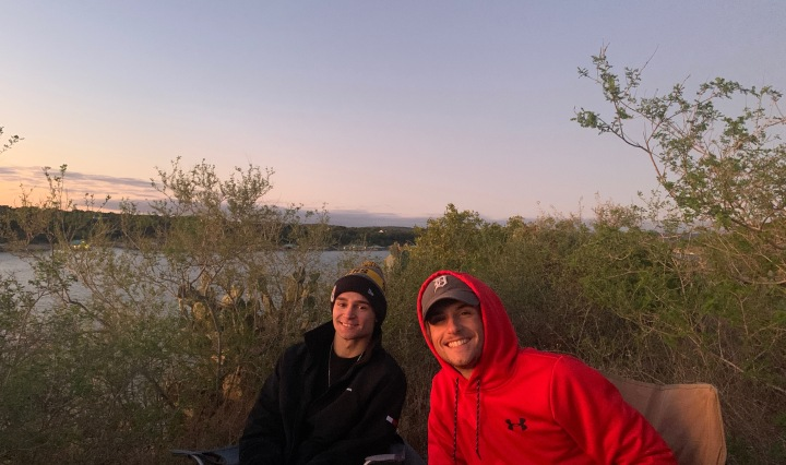 Two men sit in lawn chairs on a cliff with a sunset in the background.
