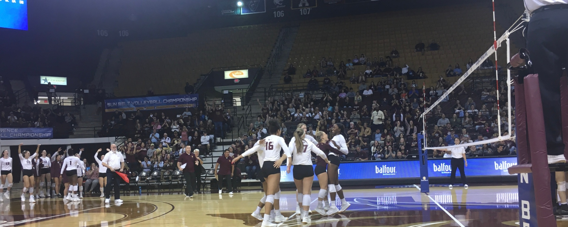 A group of girls in white jerseys gathering around in a circle to celebrate the point they just earned. One girl is being lifted up in a hug by another, this one is in a maroon jersey, to celebrate her successful block of the ball.