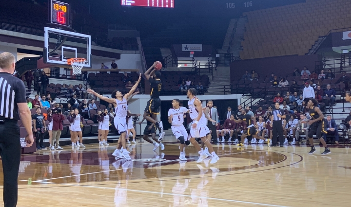 Texas State in the white uniforms defend against the shot from Cameron in the black uniforms.