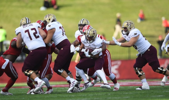 Bobcats in maroon pants, white jerseys, and gold helmets perform a handoff play to the running back.
