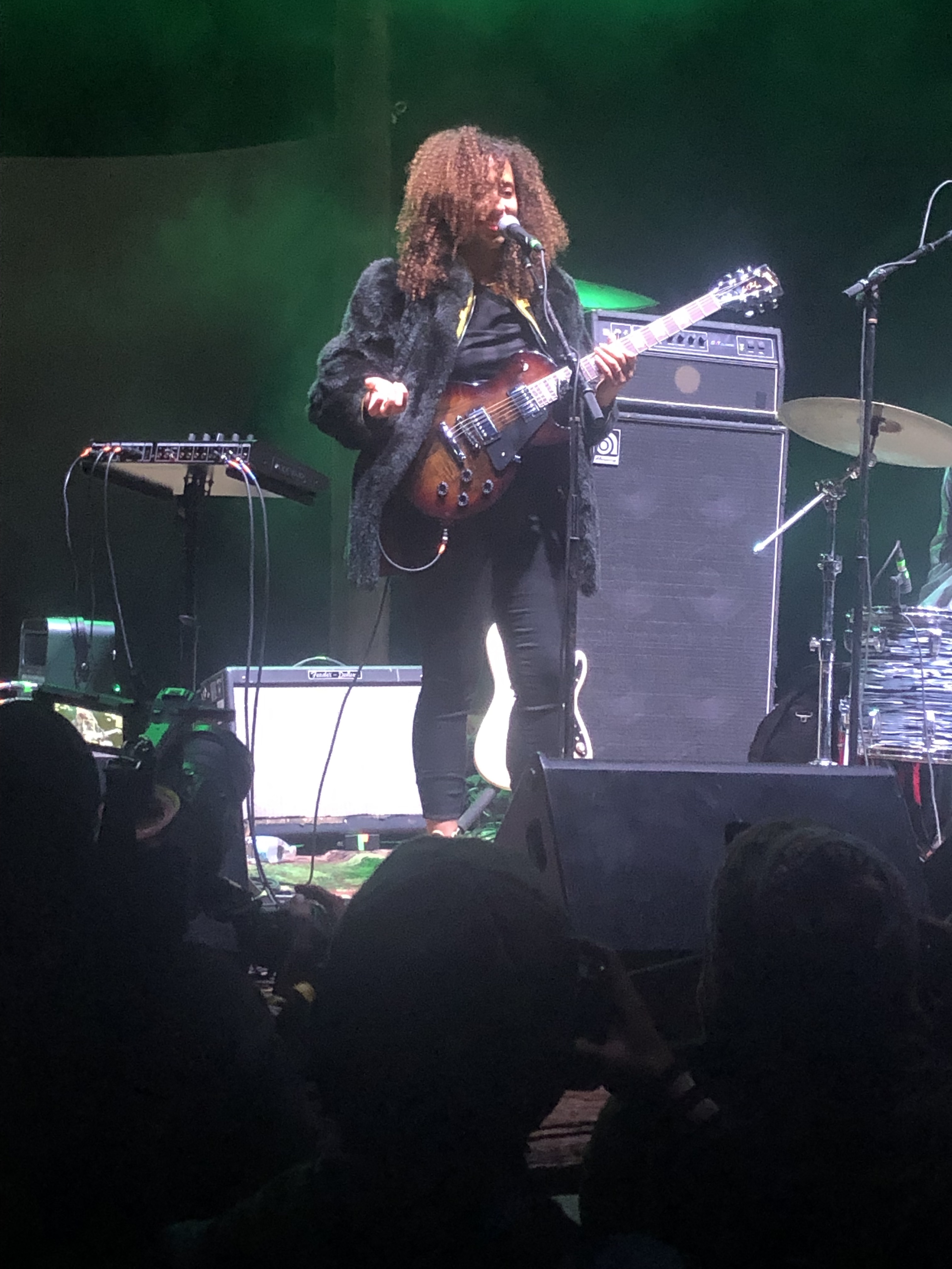 African-American female shrugging and wearing black pants, black shirt, and black coat while holding a guitar on an evening stage.