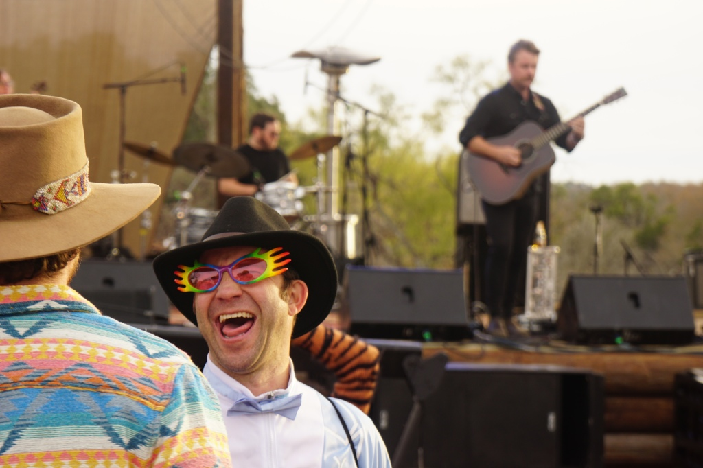 Man in rainbow hand glasses smiles at friend during Jon Stickley Trio's Performance.