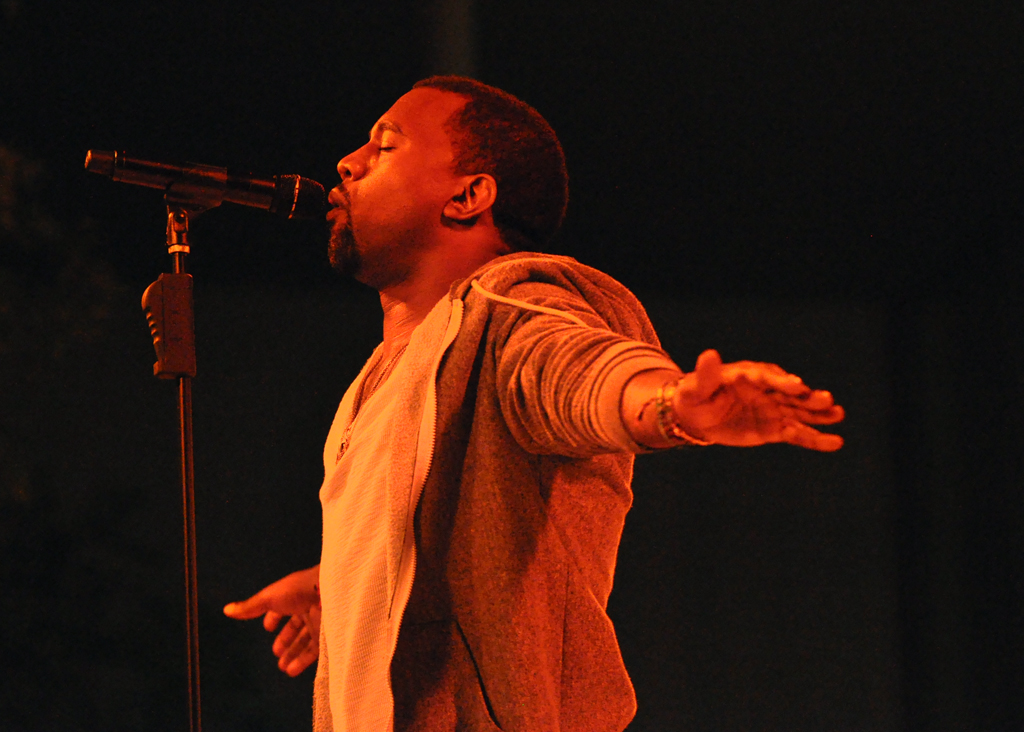Kanye West faces the left of frame, standing in front of a microphone stand singing with both arms stretched out like an airplane. The image is dark and he has an orange tint on his against a black background.