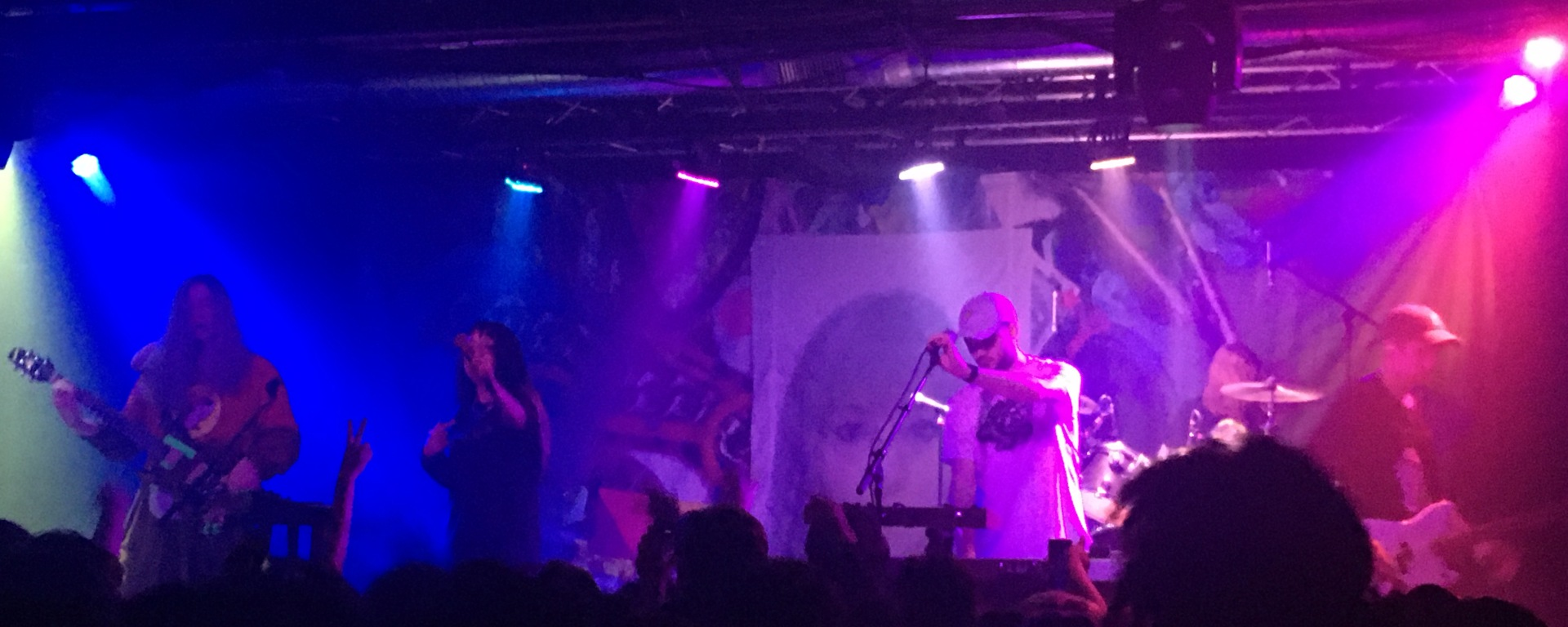 Vocalist of Kero Kero Bonito sings to the crowd, with the guitarist on the left and the rest of the band on the right. There are blue and purple stage lights flashing in the background
