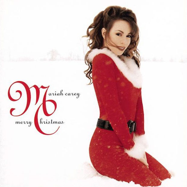 Mariah Carey sits on a white background while wearing Santa's outfit.