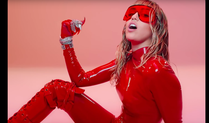 Cyrus wears a latex red bodysuit with a red background