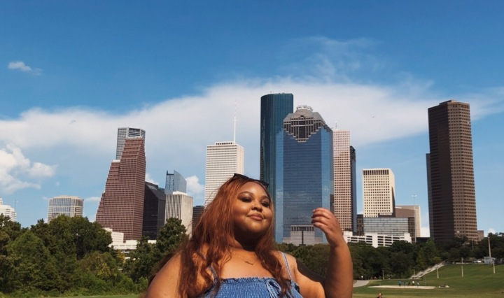 Akosua standing in front of the Houston skyline from Tinsley Park