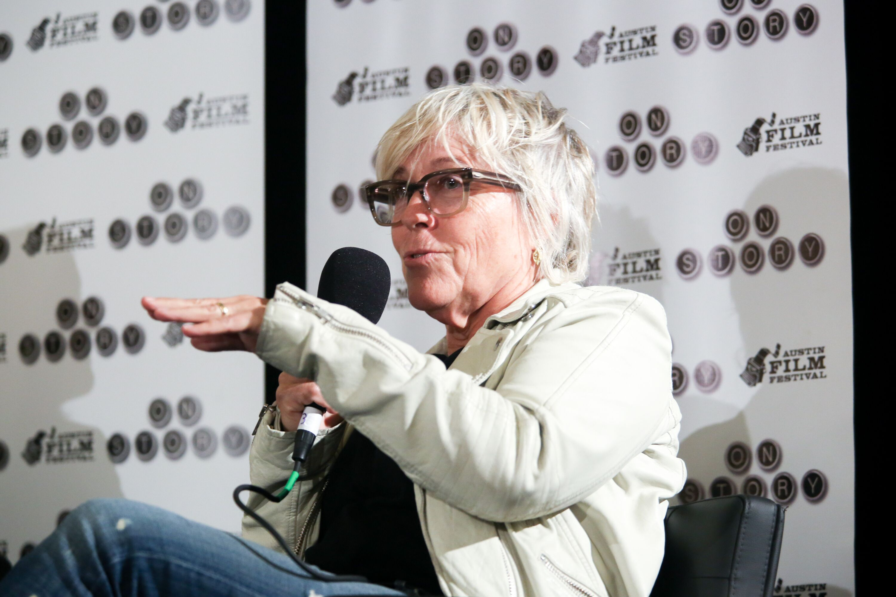 A woman with black glasses holds a microphone on stage
