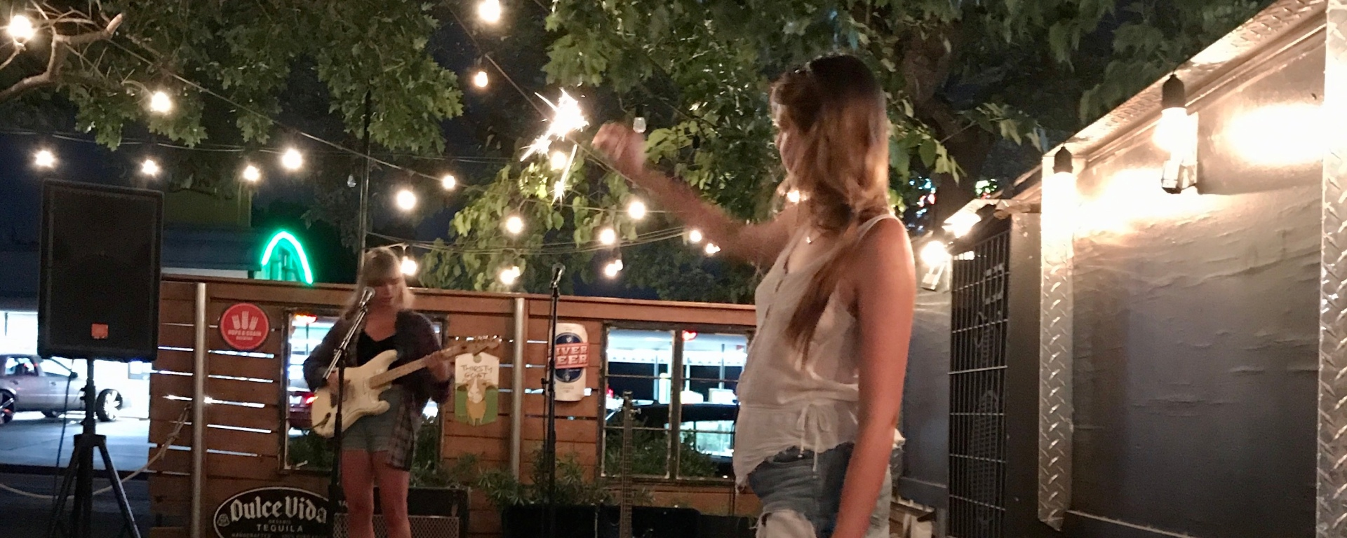 A performer stands with her guitar in the background while a patron stands in foreground holding up a sparkler