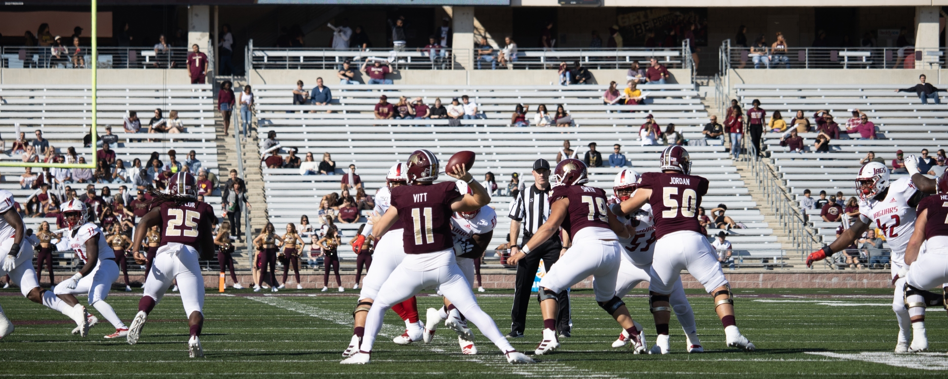 Quarterback Tyler Vitt is throwing the football off to the left behind his offensive line.
