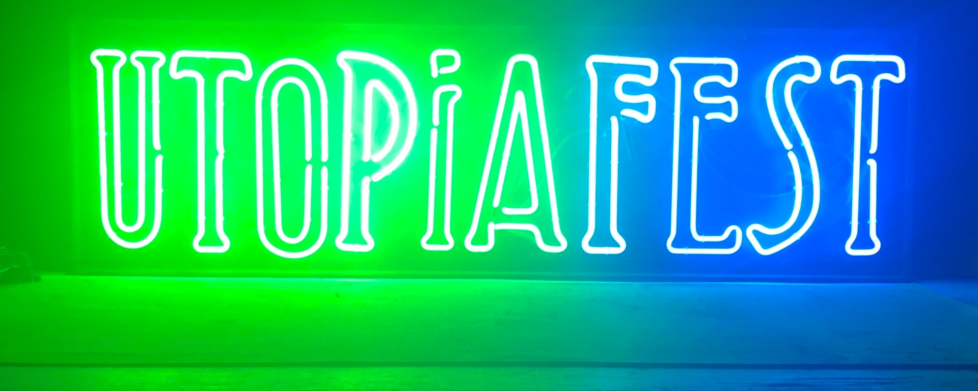 "Neon green and blue light sign that reads ""UTOPIAFEST"" in darkness."