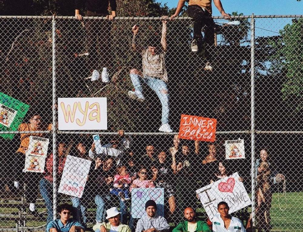 "Behind a fence are several people holding signs saying: ""I love Inner Wave,"" and ""Inner Babies."" The band sits on the ground in front of the fence along with one sign mounted on the fence which reads: ""wya."""