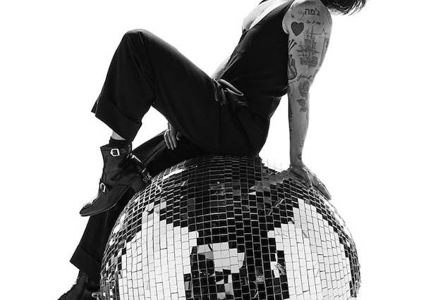 A black and white photo of Harry Styles sitting and leaning back on a disco ball