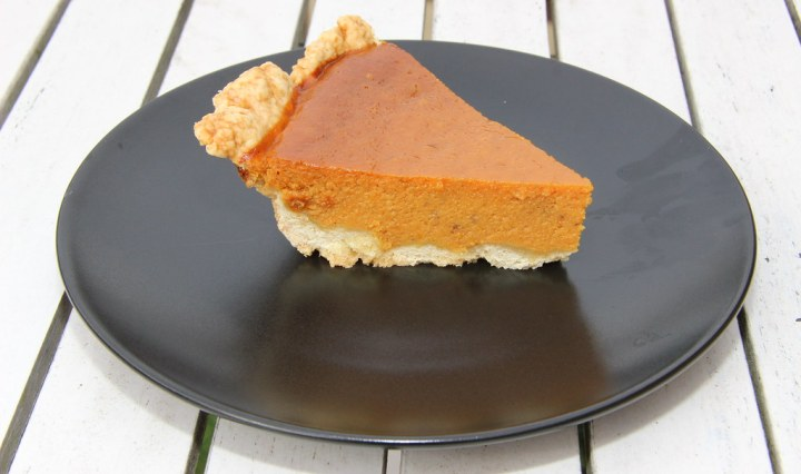 A plate with a slice of pumpkin pie sitting on a table