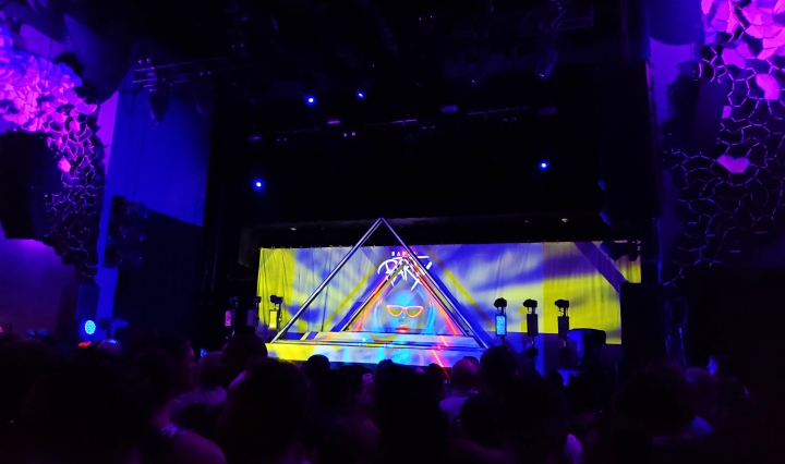 "A picture of Emo's stage. The lighting is purple, and the backdrop on the stage in a picture of Todrick Hall with red lips and sunglasses with the words ""Haus Party"" written above his head. There are two triangular fixtures on the stage."