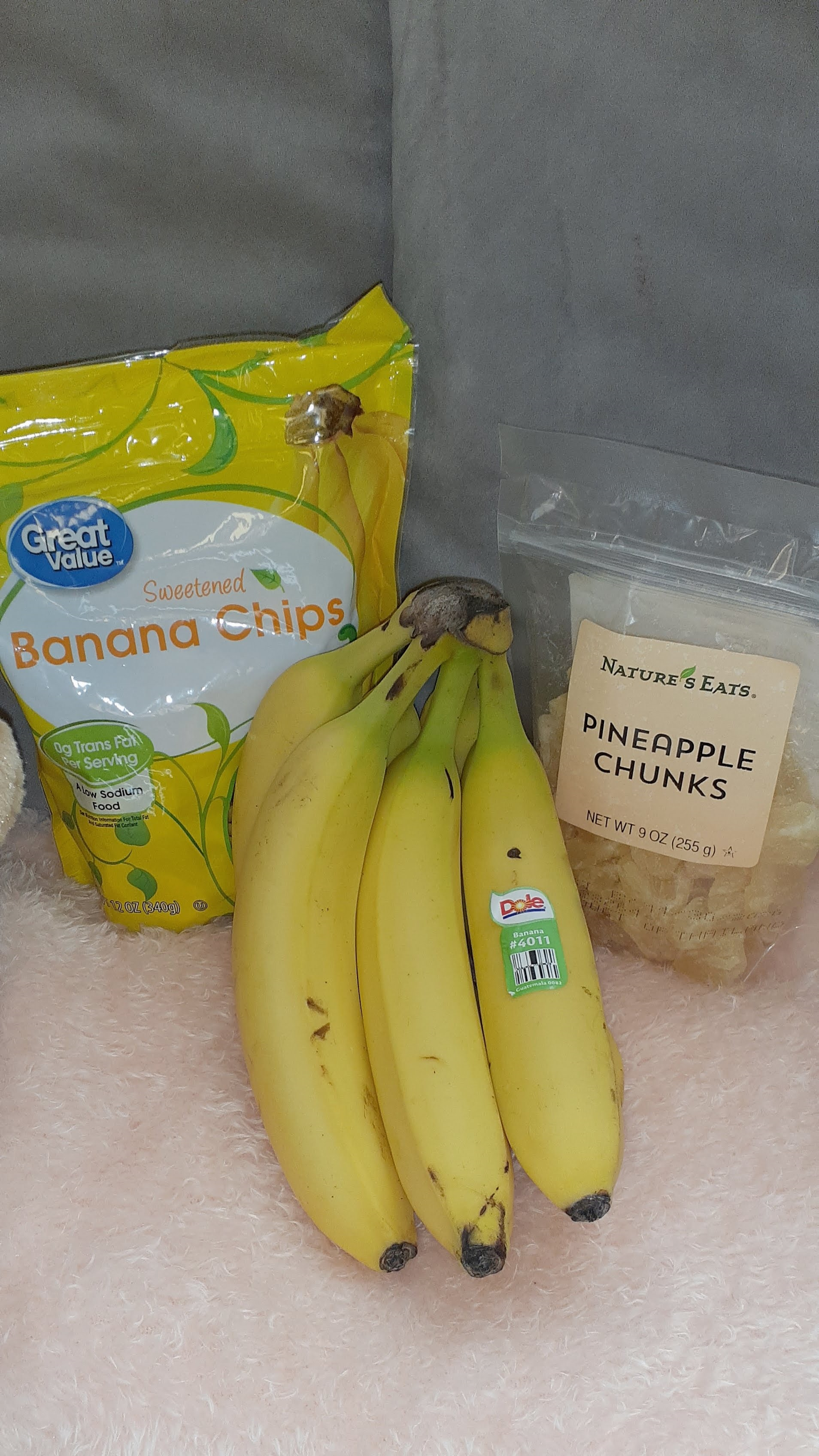 A picture of bananas, a box of granola bars, a bag of caramel rice cakes, 2 bags of pretzel chips, a jar of almond butter, a bag of almonds and dried pineapples chunks on a beige marble window sill.