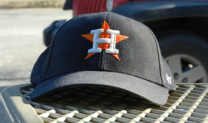 An Astros cap sits at the edge of a picnic table.