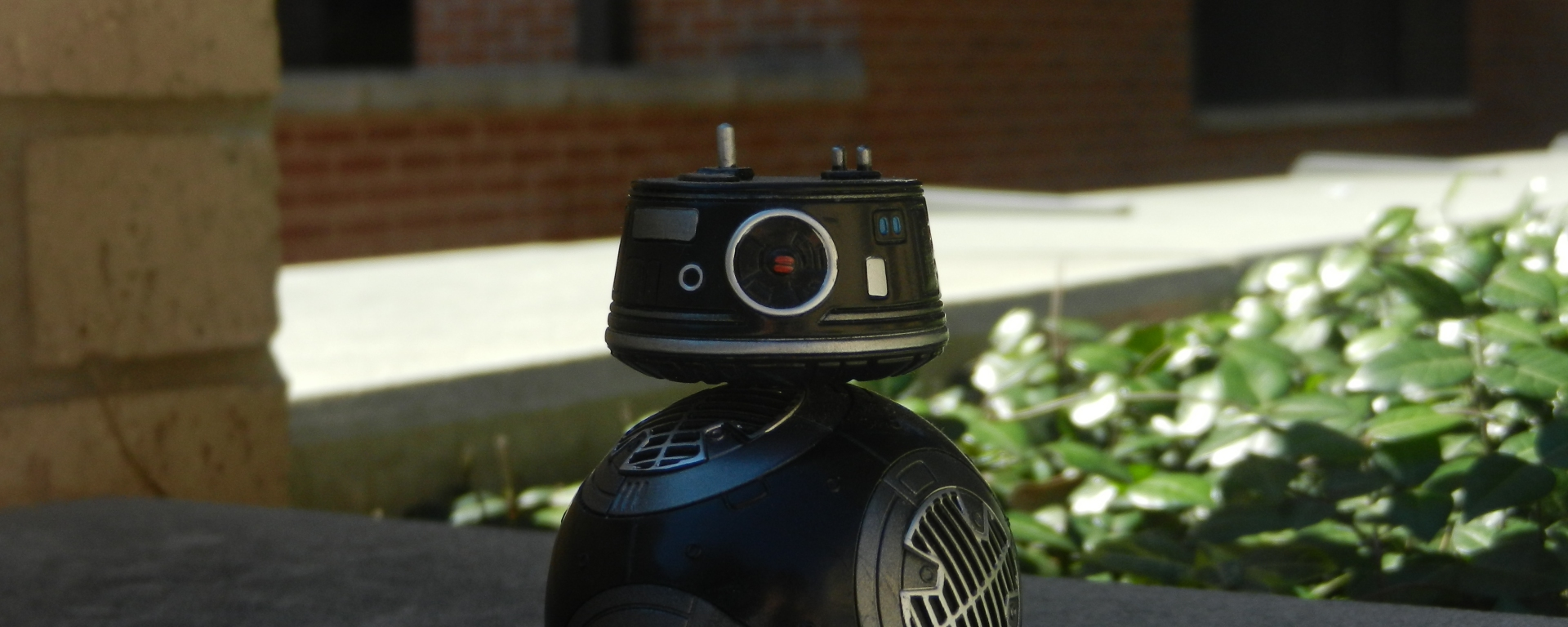 A BB-9E bobble head sits on top of a wall.