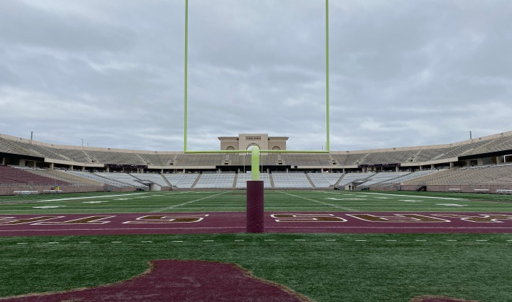 The goal post of the south end zone stands in front of the photograph with an empty stadium in the backdrop.