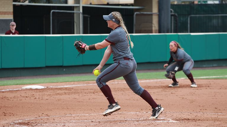 A player in a gray softball uniform is about to throw the yellow ball from her right hand while a brown pitching glove is in her left hand.