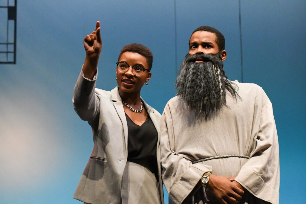 A man with a beard and woman pointing upwards are on stage.