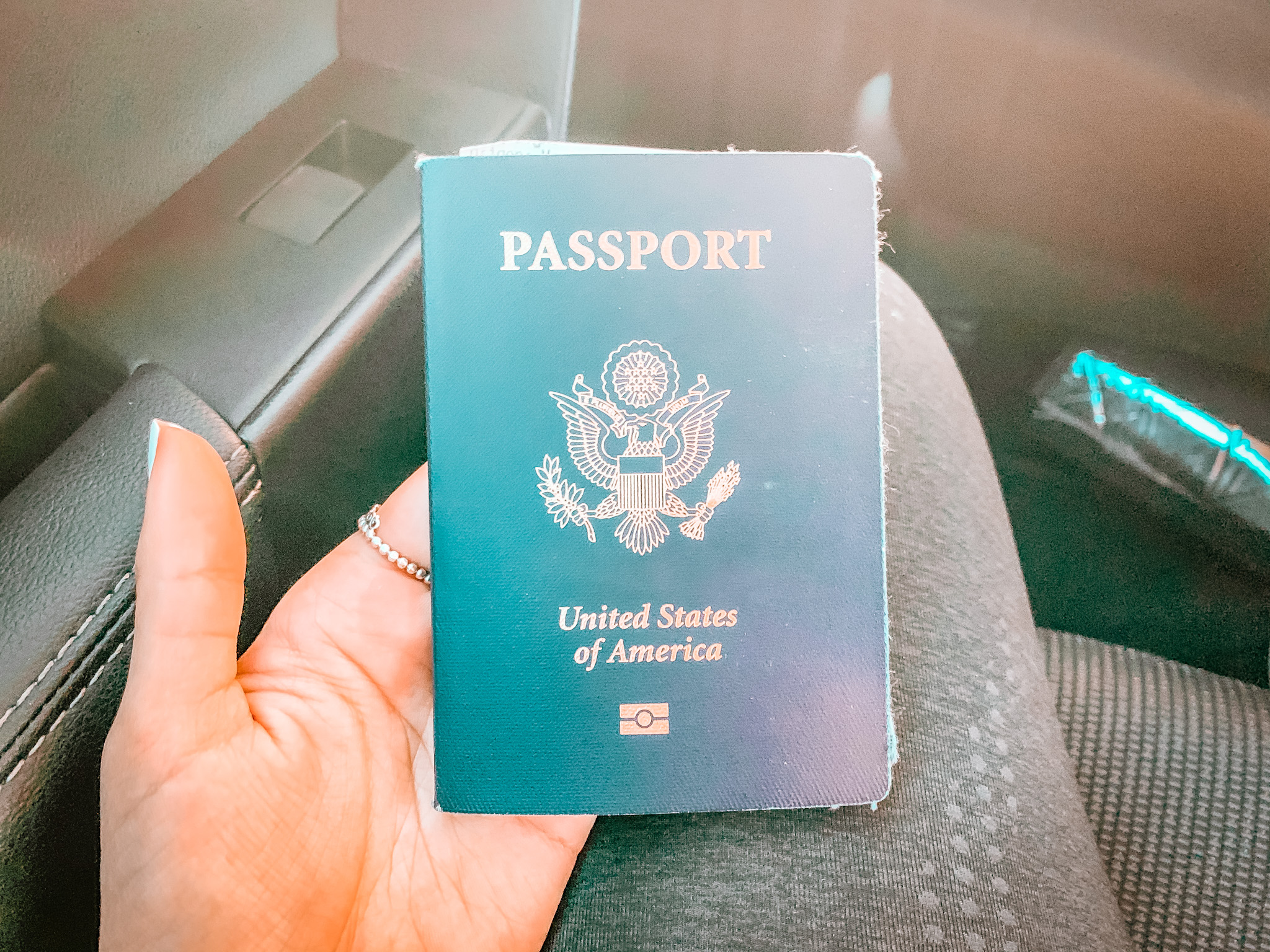 The gold United States seal with an eagle in the center is on the cover of a green American passport
