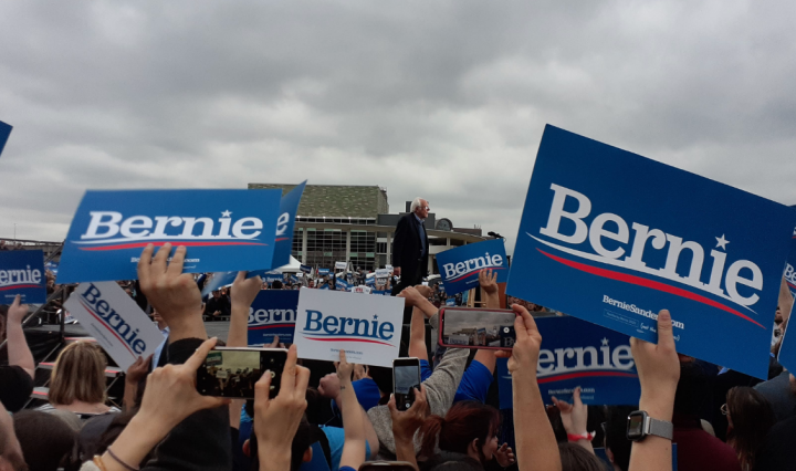 Bernie Sanders stands on a stage surrounded by people holding blue and white posters with Bernie written on them