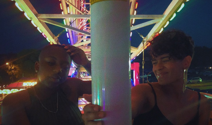 Two friends on a ferris wheel at an amusement park.