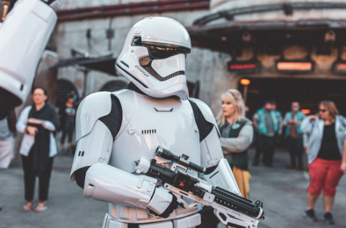A Stormtrooper walks along a road in a Disneyland theme park.