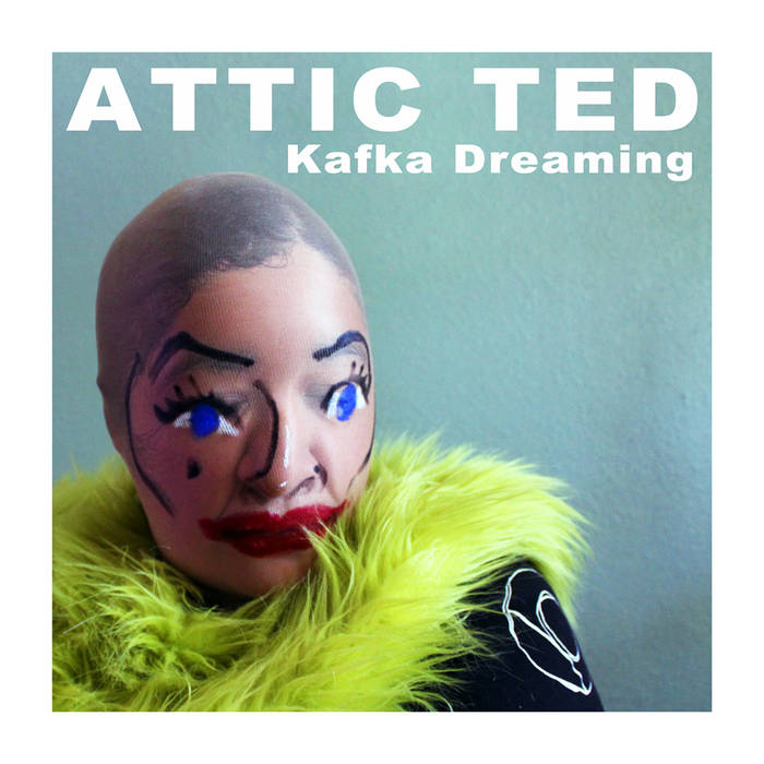 A blue background with white text that reads Attic Ted: Kafka Dreaming. A close up shot of a person wearing a mask made out of pantyhose and a green fluffy scarf is in the lower left corner.