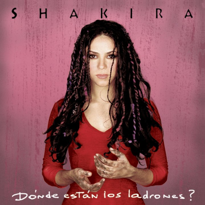 Shakira is standing in the middle of an empty room looking right at the camera. She is holding her hands out and you can see that they are covered in dirt. The album title, Donde Estan Los Ladrones? reads across the bottom.