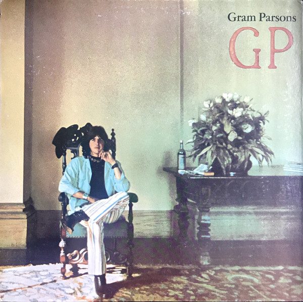 "Gram Parsons sits in an ornate chair beside a table with a large bouquet of flowers and what appears to be a wine bottle placed on top of it. The artist is wearing a blue shirt, white pants and is sitting with his leg crossed. The album's title, ""GP,"" sits in the top right hand part of the image, with the artist's name placed right about it."