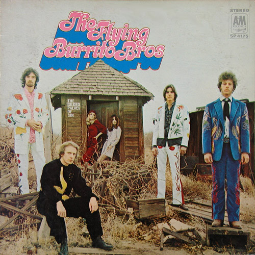 The members of the band, each in their own colorful suits, stand amongst brush and debris, while two women, one blonde, one brunette, lean against a wooden structure in the background. The name of the band, written in psychedelic pink lettering, sits above the wooden structure. The name of the album, in small, white lettering sits on the wall of the wooden structure.