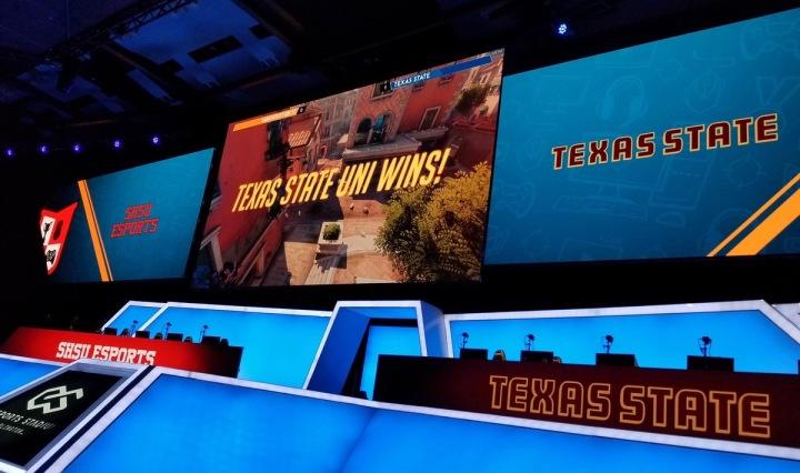 """Texas State is announced the victor on stage with a statement that says """"Texas State Wins"""". A colorful blue stage surrounds the monitors and equipment and giant screens displaying the school logos and victory statement."""