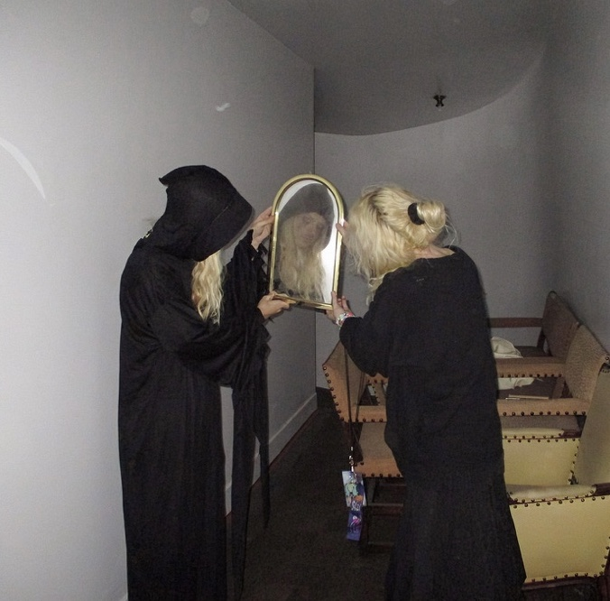 Two people in cloaks standing next to each other holding up a mirror in between them.