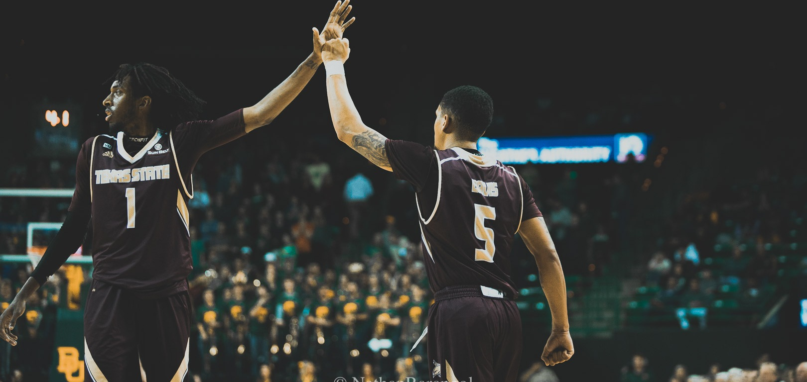 Texas State players Isaiah Small (left) high fives Marlin Davis (right) during the Bobcats non-conference road game in Waco against the Baylor Bears during the 2019-20 season with Baylor cheerleaders and fans in the background.