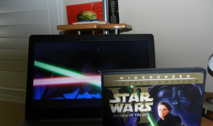 A DVD cover of Return of the Jedi displays with movie playing in background.