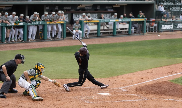 Texas State junior outfielder John Wuthrich has just hit a ball against Baylor. The ball is flying out into the playing field.