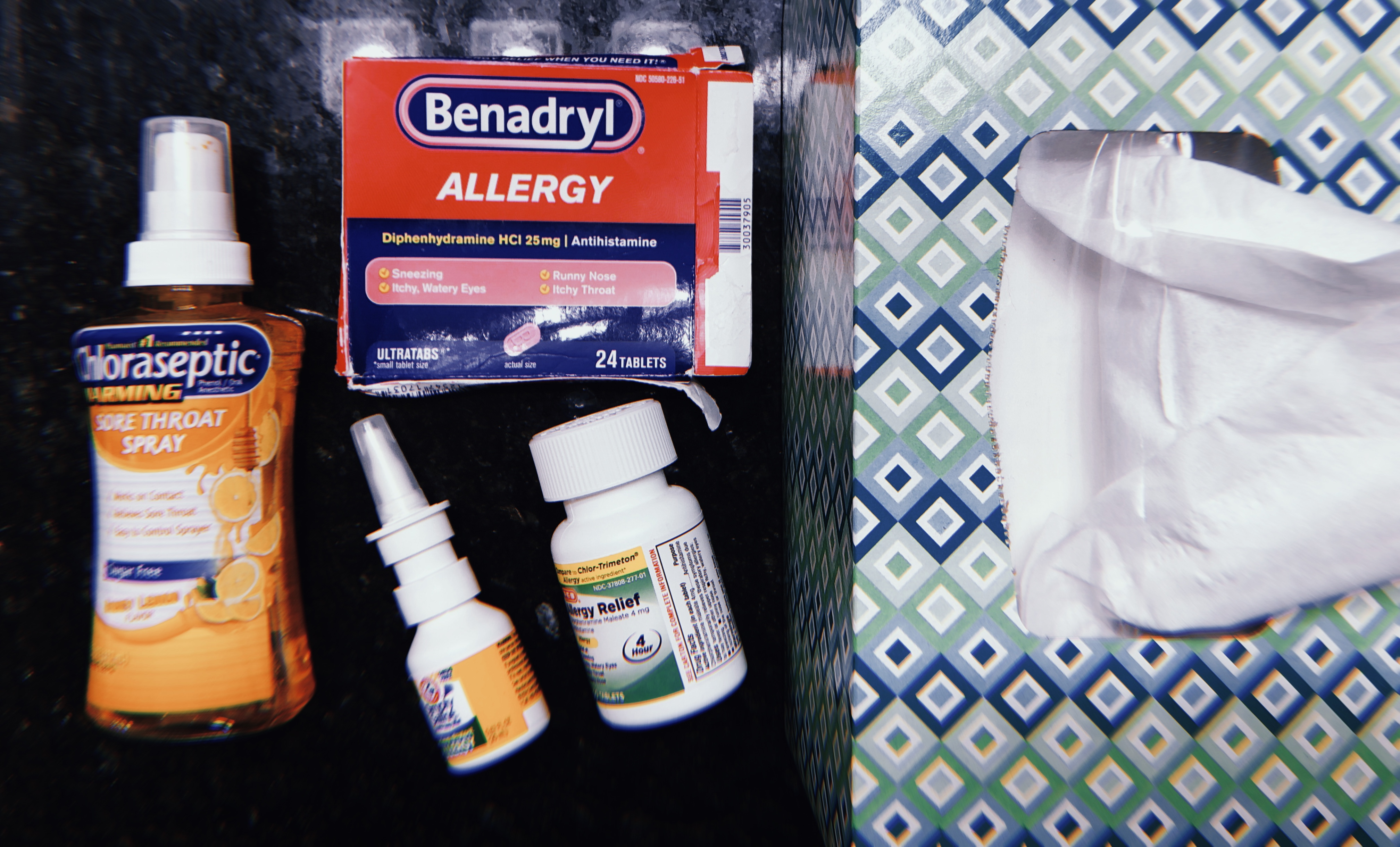 Chloraseptic throat spray, nasal spray, Benadryl, a bottle of allergy pills and a box of tissues.