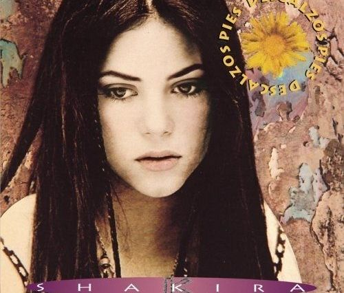 Teenage Shakira is staring off into the bottom left corner of the frame. She has long hair parted down the middle. Behind her there is a ripped wallpaper and a sunflower located at the top right of the frame spells out the album title, Pies Descalzos.