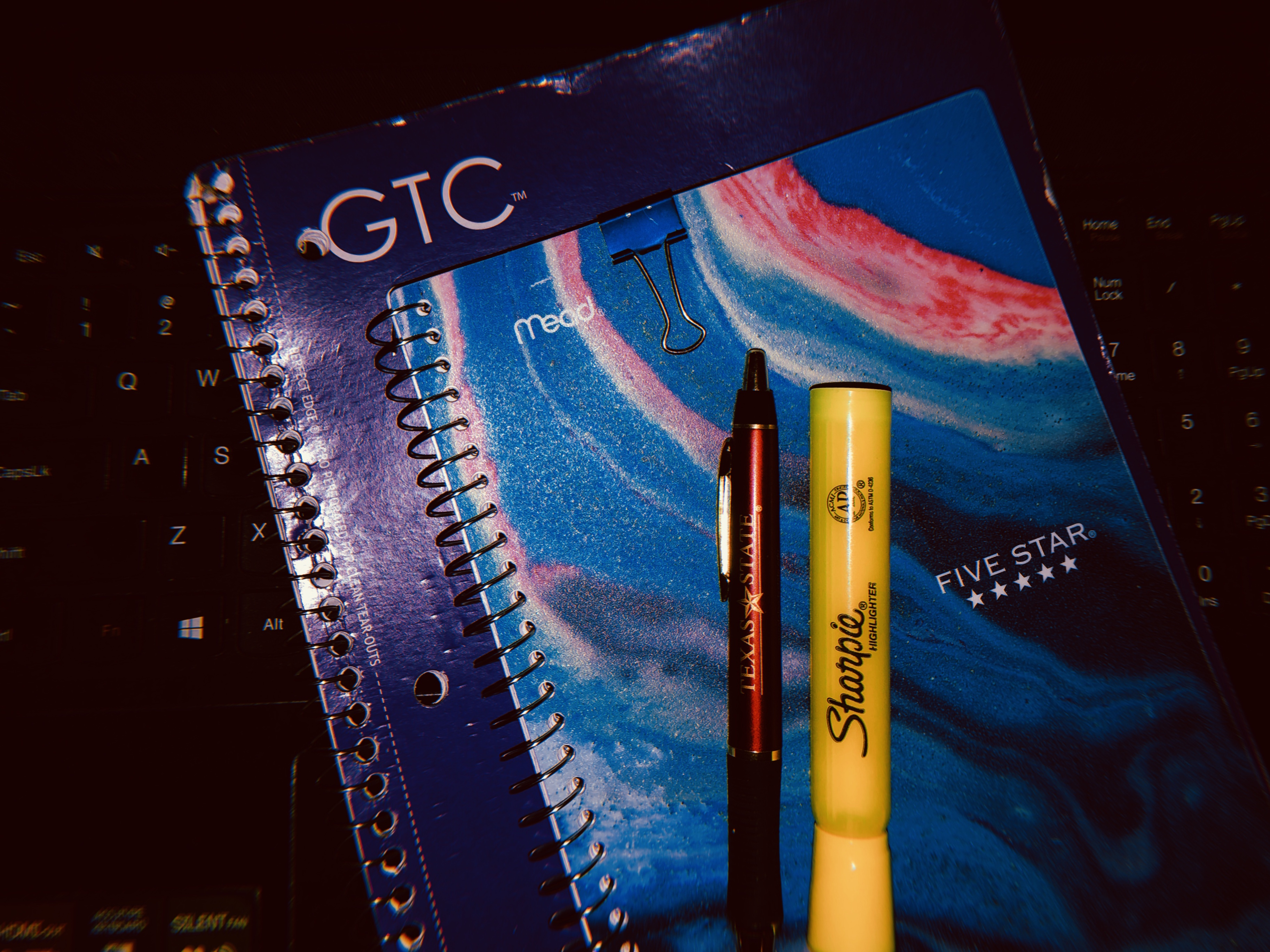 A purple spiral journal, a blue and pink marbled planner, a yellow highlighter and a pen laying on top of a laptop keyboard