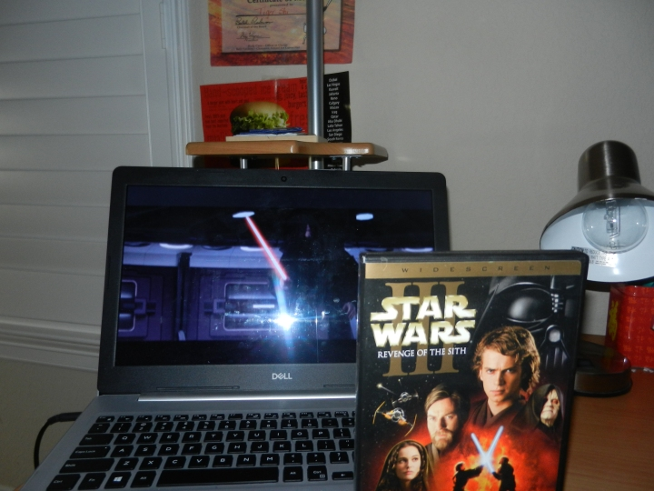 A DVD cover of Revenge of the Sith displays with movie playing in background.