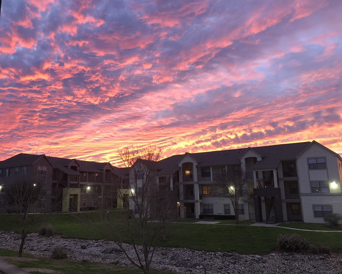 A pink, orange, purple and yellow sunset surrounding an apartment complex