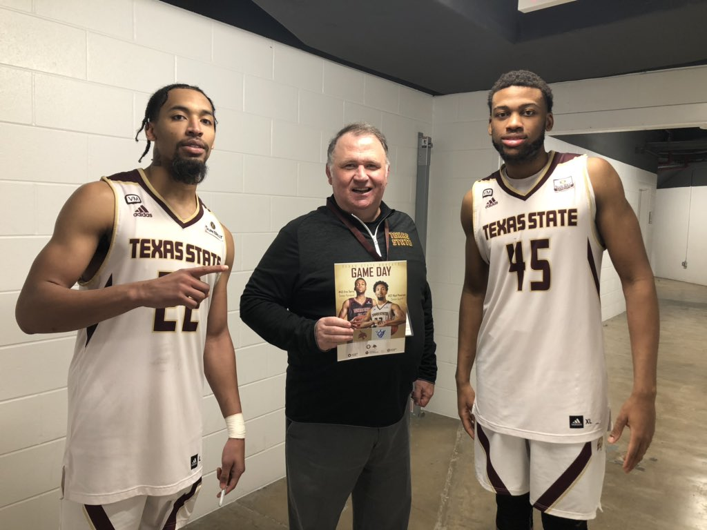 Man in black texas state shirt stands with texas state basketball players Nijal Pearson and Eric Terry wearing white jerseys.