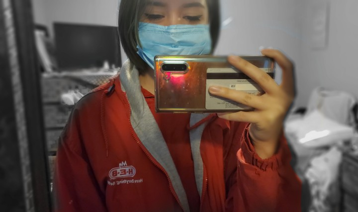 18-year-old girl wearing a red jacket taking a picture in front of the mirror