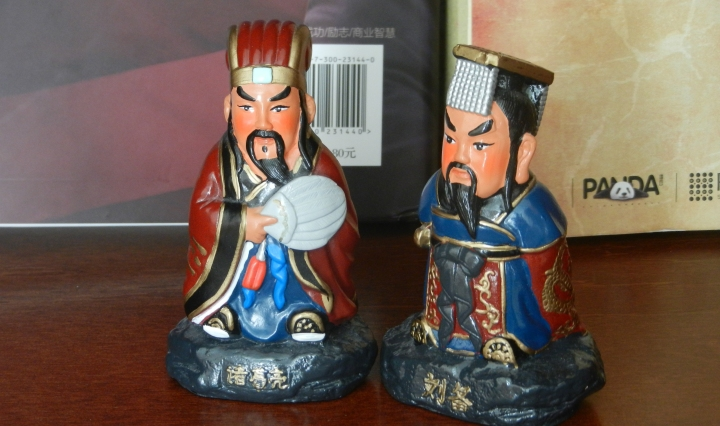 Two figurines of Chinese historical leaders sit on a bookshelf.