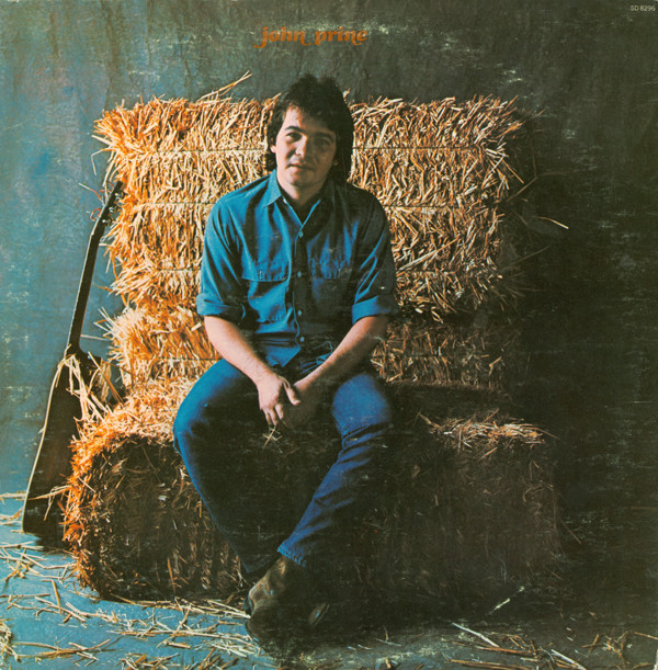 The artist sits atop a bale of hay with his guitar leaned against the left side of the bail. The artist's name is displayed in the top center of the image.