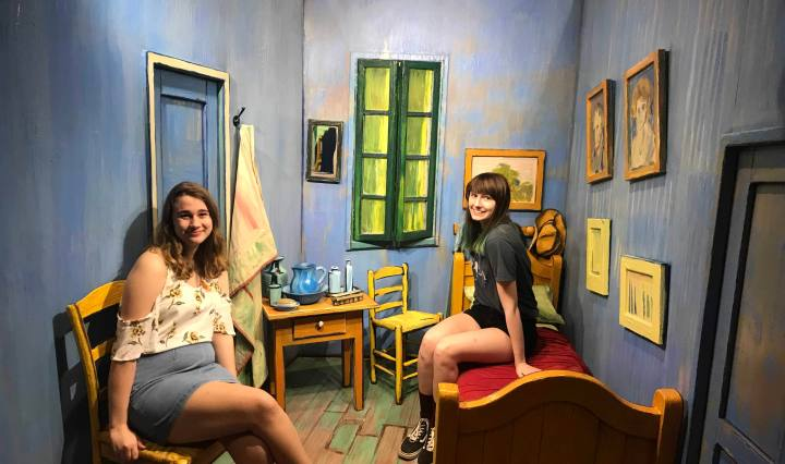 Two young women sitting in front of a backdrop designed to resemble one of Vincent Van Gogh's paintings.