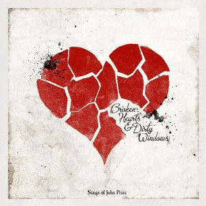 "Several small red pieces form to make a heart atop a grey background. The album title is located on the heart, with the words ""Songs of John Prine"" located in the bottom center of the image."