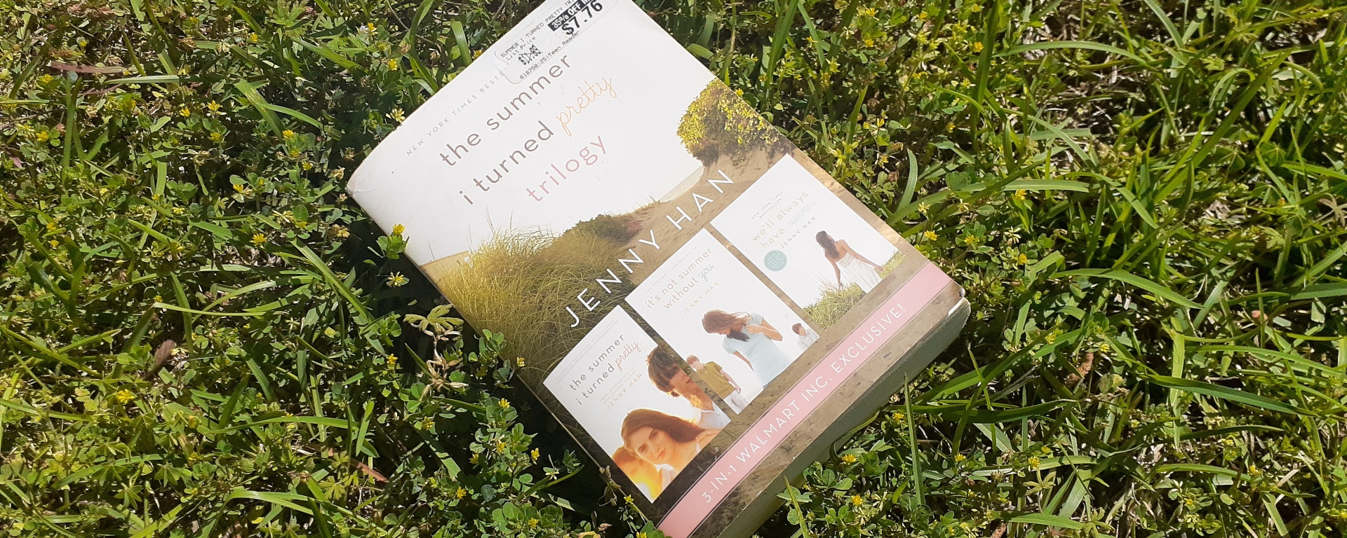 a big white book with a girl and two boys on the cover lies in the grass in the sun